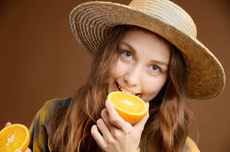 A young attractive Caucasian woman with long hair, in denim overalls and a straw hat, holds a cut orange in her hands and looks into the camera.