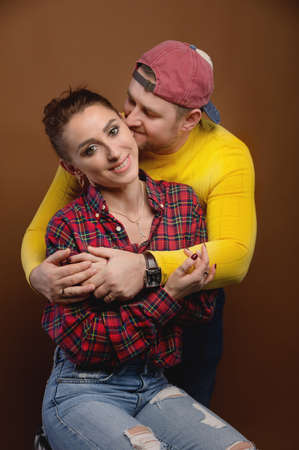 Caucasian married couple man and woman hugging and kissing eyes closed. Casual style and bright clothes of an ordinary 30-year-old couple studio portrait Foto de archivo