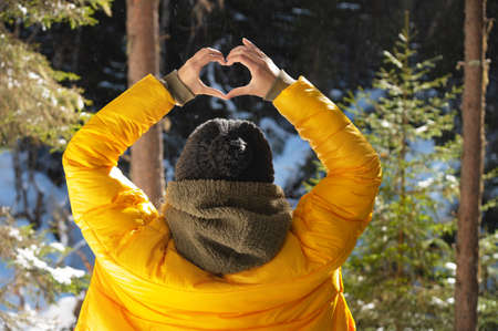 young caucasian woman and shows fingers gesture of heart, love at eye level. Back view in forest
