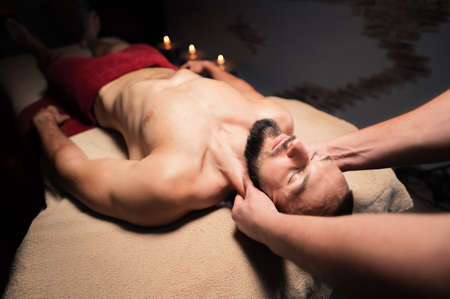 In a professional massage parlor, a Caucasian male athlete with a beard is kneading the neck. Sports massage of the lateral longitudinal muscles of the neck