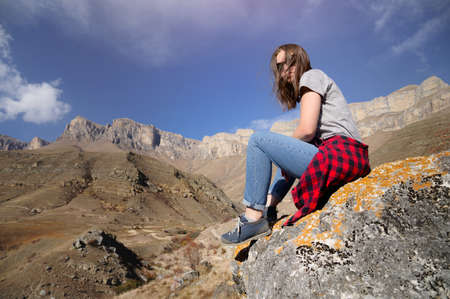 happy attractive hipster traveler girl with windy hair and smiling on a background of sunny mountains. place for text. travel and wanderlust