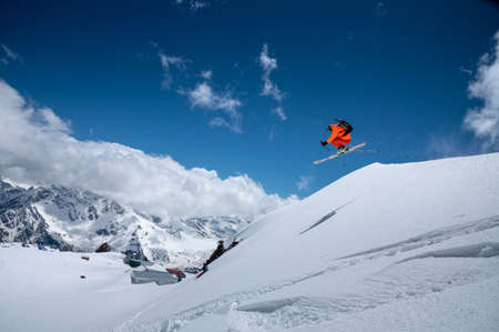 Professional athlete young male skier in an orange ski suit flies over the mountains after jumping from snow-covered ledges. Freeride sports community against the backdrop of snow-capped peaks