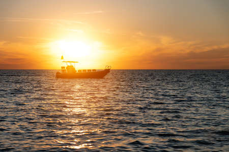 Small fishing boat catamaran at sunset. Sea transport without people in the sunset light. Twilight at sea