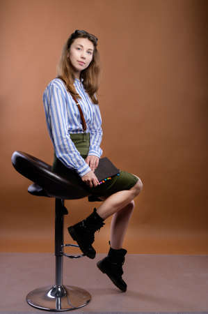 Portrait of an attractive Caucasian student or business woman with a notepad sits on a bar stool and looks into the camera. Business portrait.