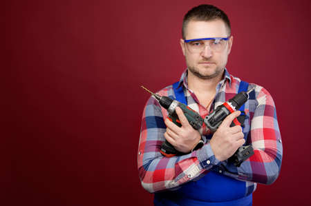 serious Caucasian repairman in goggles holding woodworking tools. Carpenter portrait on red studio background