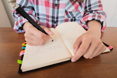 Young Caucasian attractive woman taking notes in her notebook while sitting in the kitchen at the table. Paper notebook writing female hands Stockfoto