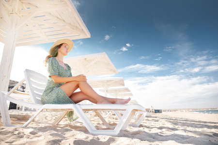 A blonde in a green dress sits on a sunbed and looks at the seascape under protective sunny wooden umbrellas. Young caucasian attractive woman by the sea on the beach Stockfoto