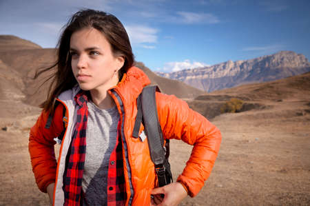 Portrait of a young Caucasian attractive woman standing in a backpack on the background of a rocky mountain peak looks to the side while adjusting her jacket