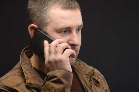 Close-up portrait of a caucasian businessman in a casual jacket talking on the phone upset looking to the side and down. A distressed man is sad with a phone in his hand. Studio shot