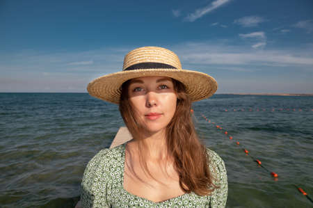 Beauty at the sea portrait of a beautiful woman in a hat close-up. Attractive portrait of a fashionable girl with the rays of the sun on her face against the background of the sea and sky