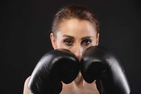 Young caucasian sportswoman in sportswear and large black boxing gloves looks into the camera and covers her face with gloves. Copy space Stockfoto