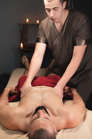 Professional masseur doing sports chest massage to an athlete to a client man Stockfoto