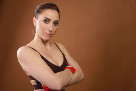 Portrait of a strong athletic woman. She stands with her arms folded on her chest and looks at the camera. Fitness sport and gymnastics copy space