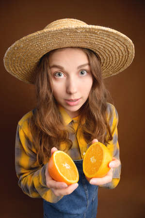 Surprised young woman looks at the camera and holds a cut orange in her hands. Healthy food and fruits in the diet