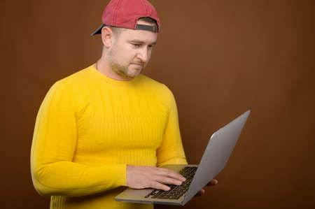 Pleasant caucasian mature casual man using laptop in studio. Use of electronics
