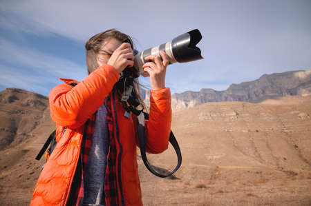 Caucasian woman landscape photographer with big lens and professional camera takes pictures in mountains against background of epic rocks