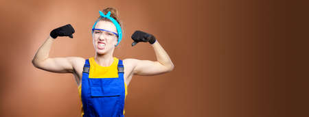 Young beautiful caucasian woman repairman worker with blue eyes in uniform showing arm muscles, proudly smiling and making a strong grimace. contractors and wise construction superintendents.