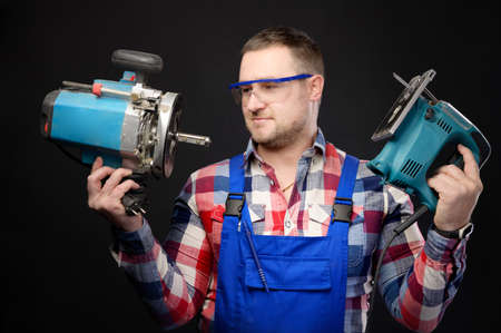 A professional carpenter in uniform and goggles holds an electric tool, a jigsaw and a milling cutter. Studio portrait on black background