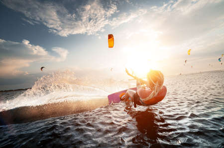 Professional kite surfer woman rides on a board with a plank in her hands on a leman lake with sea water at sunset. Water splashes and sun glare. Water sports