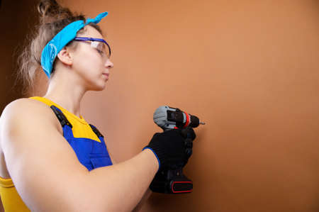 Young woman repairman in overalls and goggles works with a screwdriver in the studio on a brown background. Focus on the screwdriver. Copy space Stockfoto