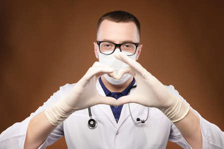 Portrait of young male doctor in glasses holding heart gesture in studio on gray background