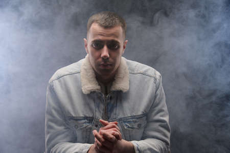 A man with a darkened face sits in a dark studio filled with smoke. Smoking problem. Nicotine addiction