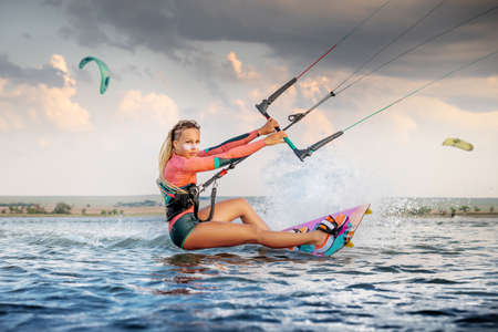 Front view Professional kite surfer woman rides on a board with a plank in her hands on a leman lake with sea water at evening. Water splashes and sun glare. Water sports