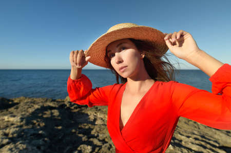 Lovely romantic caucasian young woman in red dress and straw hat against the background of the sea horizon in windy weather Foto de archivo