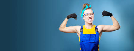 Panoramic shot. beautiful caucasian female repairman with blue eyes in uniform shows arm muscles, proudly smiles and makes a strong grimace. Studio shot on light blue background Foto de archivo