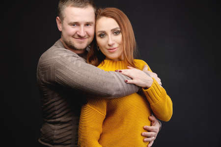 Portrait of attractive Caucasian married couple man and woman hugging over black background. Happy family relationships Zdjęcie Seryjne