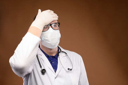 Male Caucasian doctor in white medical uniform shows face palm gesture. Chagrin and disappointment. Copy space