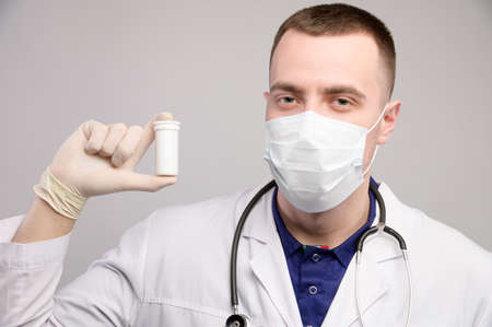 Young caucasian doctor man in a mask and white coat is holding a package with unknown pills. Doctors recommendation of medications Foto de archivo