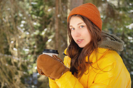 Attractive Caucasian positive young woman in winter clothes in a hat with mittens and a down jacket stands in a coniferous winter forest with a paper cup of coffee or tea.