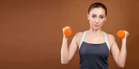 Panoramic shot of an athletic caucasian woman with dumbbells in her hands. Stands on a brown background with dumbbells in his hands and looks at the camera