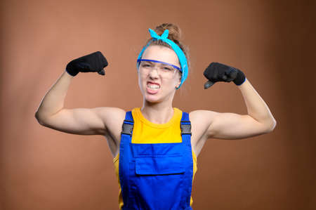 Portrait of a strong attractive Caucasian young woman in construction worker workwear and safety goggles. Demonstrates his strength by showing biceps and making a grimace. Looks into the camera