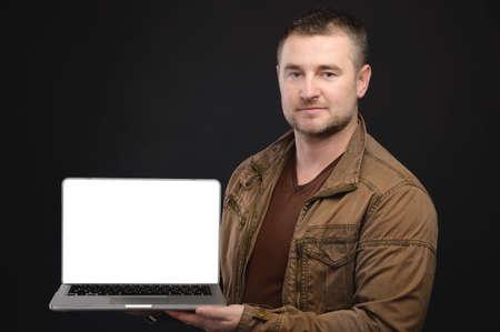 Portrait of casual friendly Caucasian man holding laptop with cut out screen. Laptop presentation. Studio portrait Zdjęcie Seryjne
