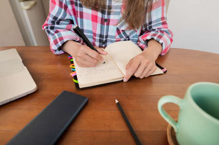 Young woman sitting at the kitchen table makes notes in a notebook. Home Office. Caucasian girl being homeschooled Zdjęcie Seryjne