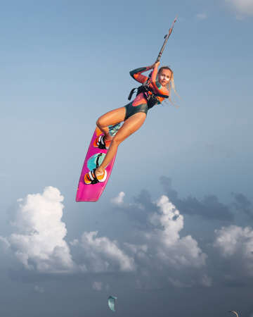 Professional athlete kitesurfer young caucasian woman doing a trick in the air against the backdrop of the sunset sky and clouds. Professional kitesurfing and kite culture training