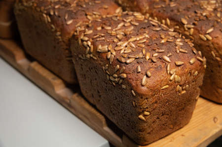 fresh brown loaves of rye bread in the form of bricks with sunflower seeds on a crust. Lie on a wooden rack Zdjęcie Seryjne