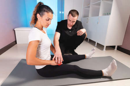 Young caucasian male masseur showing and controlling myofascial massage of the fascia of the legs to a female client. Self-massage training using a massage ball Foto de archivo
