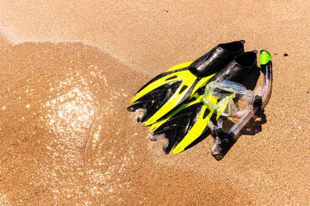 Snorkeling equipment on the sand with ocean waves splashing the water. Black fins, black mask, snorkel on sandy texture background. Items lying in the sand
