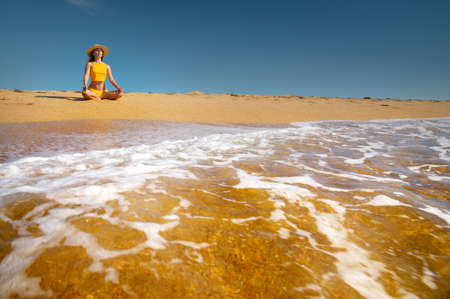 Young caucasian woman sits in lotus position on a golden beach by the ocean. Girl in a hat on the seashore meditates