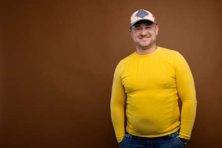 Portrait of an attractive friendly Caucasian man in a cap and yellow sweater on a brown background. Nice middle aged guy in casual clothes. Looks into the camera. Copy space
