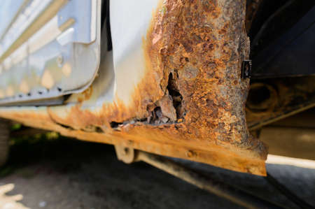 Body repair and welding work required. Rust on a gray old car. Rust hole on an old worn out painted metal surface. Zdjęcie Seryjne