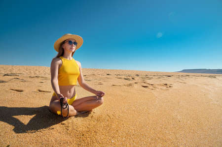 Meditation among the golden sands of the desert. Young caucasian woman in a yellow swimsuit and a straw hat sits in a lotus position on the sand with a rosary in her hand against the blue sky