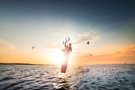 Young caucasian woman kitesurfer doing a jump trick on a sunset background. The girl hides the setting sun in a jump. double-sided copy space. Central composition. Kitesurfer spot