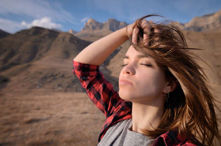 Portrait of attractive caucasian young woman enjoying closed eyes stands in the mountains against the background of epic rocks