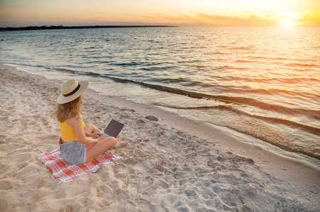 Wide angle Young caucasian woman in shorts and a straw hat uses her laptop while sitting on the sandy beach by the sea at sunset. Freelancer and remote work