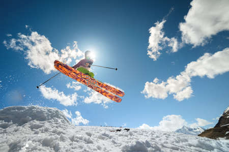 A woman skier makes a jump trick, covering the sun. Flying skier against the background of the sky and clouds. Foto de archivo
