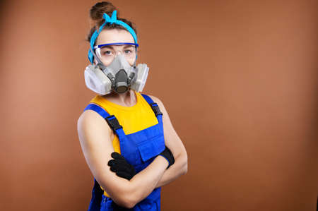 Portrait of Caucasian young woman builder. The arms are folded over the chest. Wearing protective goggles and a respirator wearing a respirator mask. Copy space for text or logo